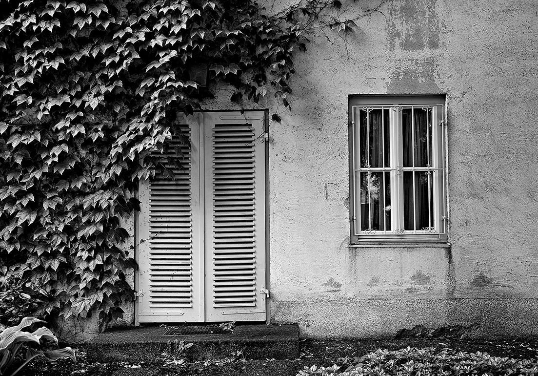 mit Schlagladen verschlossene Tür zum Garten und vergittertes Fenster an einem Wohnhaus