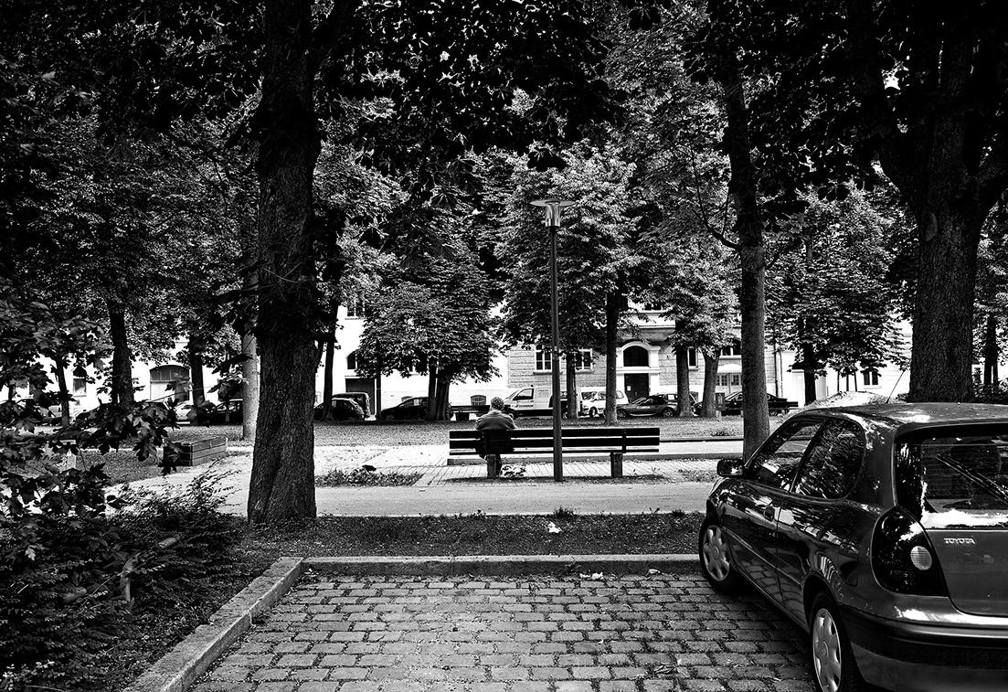 parkendes Auto, Mann auf einer Parkbank im Westend, München, Bayern, Deutschland