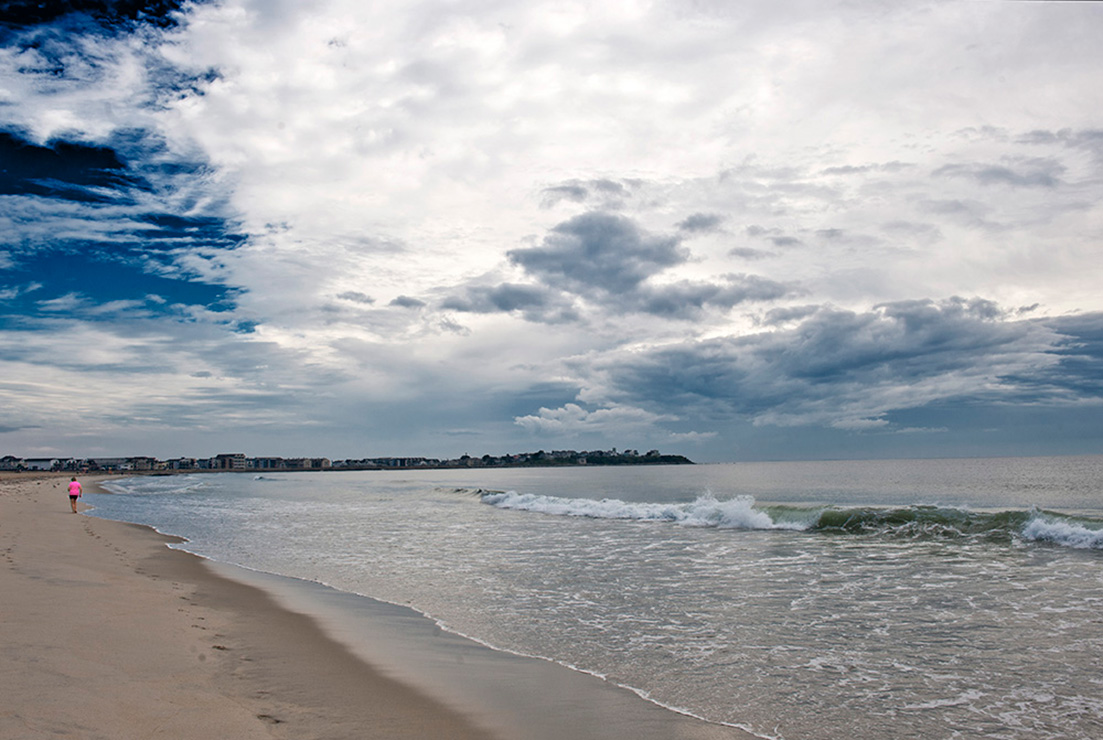 Hampton Beach; New Hampshire; USA, Strandläuferin in pinkfarbenem Top, einsam, Strand, Wolken, Himmel, Meer
