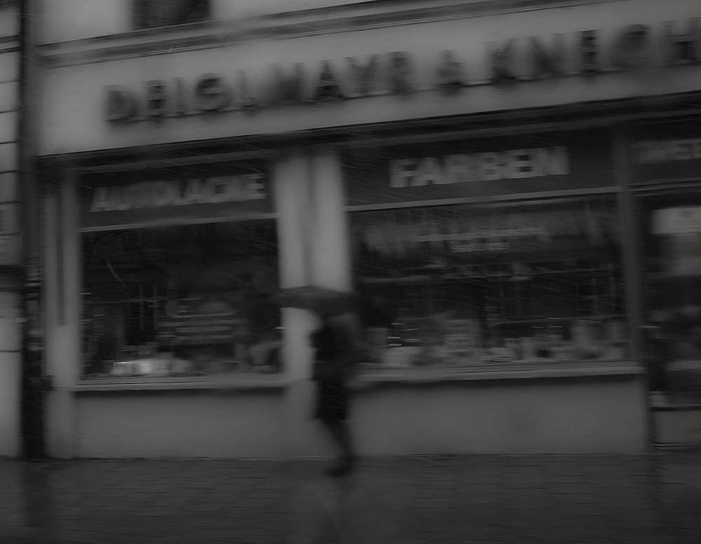 Schwarzweißfoto, Mensch mit Regenschirm, vor Laden, verschwommen, Foto : Azucena Viloria